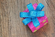 Christmas gift box with blue bow on a wooden texture closeup.