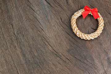 Straw Christmas wreath on a wooden texture.