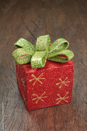 Christmas gift box with a bow on a wooden texture.