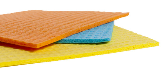 Three different color sponges on a white background