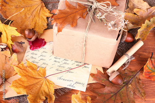 autumn background: vintage gift, letter and leaves