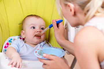 mother spoon feeding her baby boy