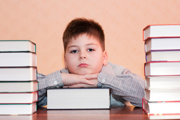 Tired kid with a stack of books
