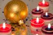 Goldene Weihnachtsbaumkugel und Kerzen