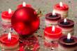 Rote Weihnachtsbaumkugel und Kerzen