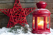 Christmas red star and lantern in night on snow with fir