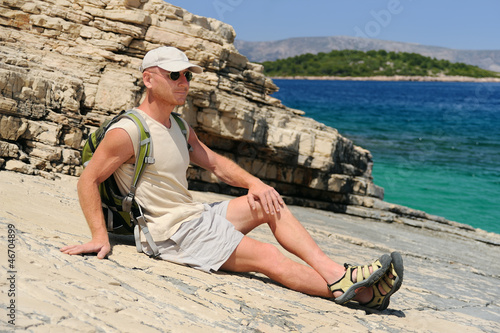 Outdoor man resting on rock after hiking, Croatia