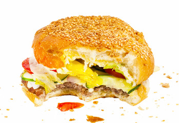 Bitten burger with vegetables and crumbs isolated on white