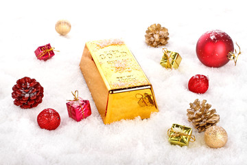 Golden bar as christmas present in the snow with ornaments