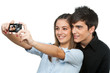 Young couple taking auto portrait with camera.