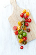 Assorted colorful cherry tomatoes on cutting board