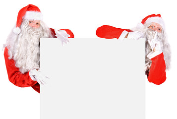 Two Santa Claus holding a blank sign