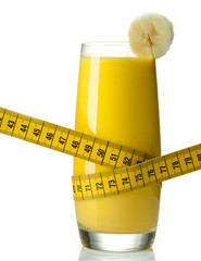 Tasty banana smoothie with yellow measuring tape around the glas
