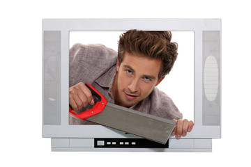Man with a saw inside a television set
