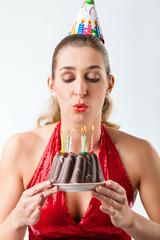 Frau hat Geburtstag Torte mit Kerzen und pustet