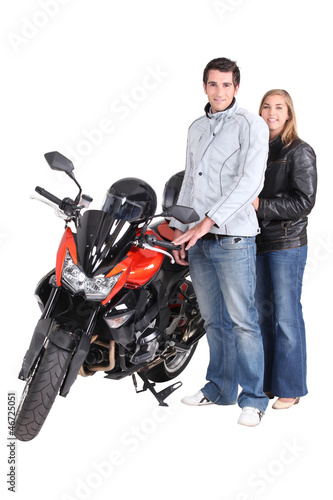 Couple stood by motorbike