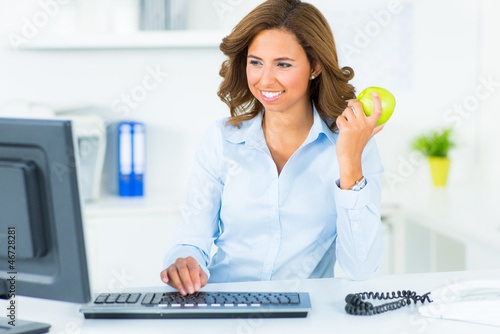 junge frau isst einen apfel beim arbeiten