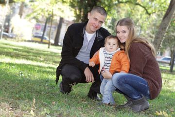 young happy family with child, outdoor portrait on natural backg