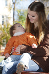 young happy mother with child, outdoor portrait on natural backg