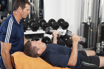Senior male being spotted by personal trainer