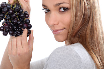 a young woman savouring sensually a grape