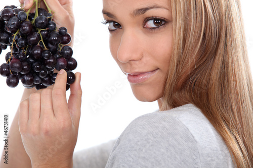 a young woman savouring sensually a grape