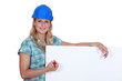 Female builder writing on blank poster