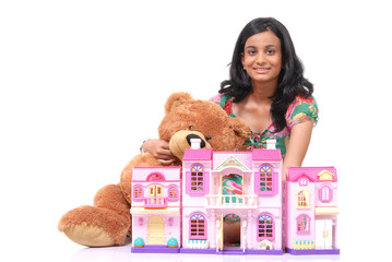Girl with teddy bear and toy house