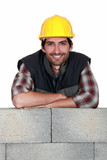 Smiling tradesman leaning on a stone wall poster