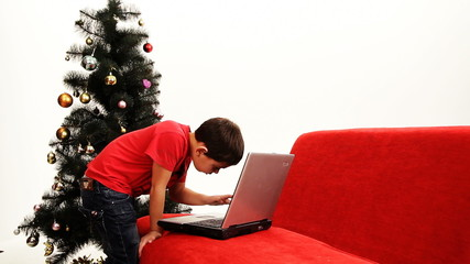 A boy and a girl playing with their mother's laptop