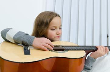 Mädchen spielt konzentriert Gitarre