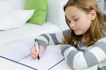 Mädchen schreibt etwas in ein Buch