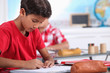 little boy focusing on his work in classroom