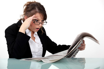 Woman staring at the newspaper in disbelief