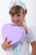 Young girl dressed as a princess and holding a heart-shaped box