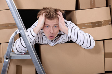 Man surrounded by stacks of cardboards