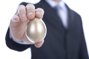 Businessman holding golden egg, close up