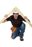Smiling carpenter holding timber frame