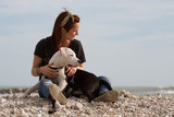 beautiful young woman embracing dog looking at the sea