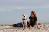 beautiful young woman sitting with dog at the sea