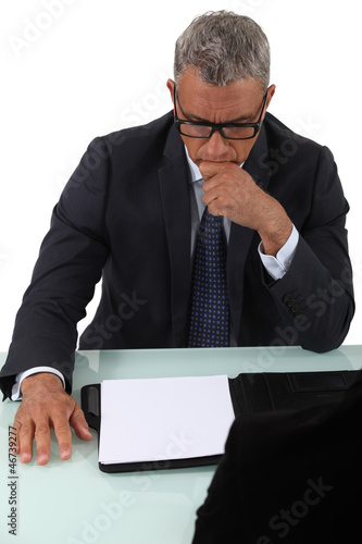 Concentrated man looking at a sheet of paper