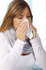 Hübsche Frau putzt sich die Nase mit einem Papiertaschentuch