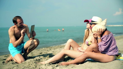 Group of friends taking photo with tablet computer on the beach