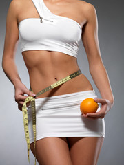Beauty female body with measuring tape and orange