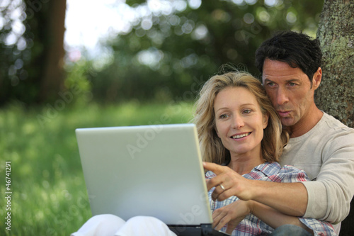 Couple with computer in the garden
