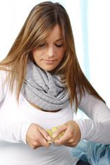 Junge Frau drückt eine Tablette aus einer Blisterpackung
