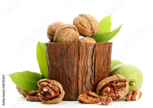walnuts with green leaves in woooden vase, isolated on white