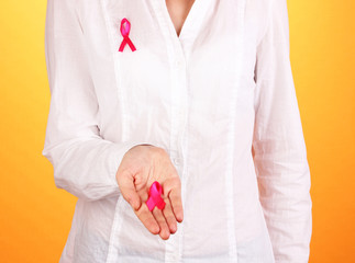 Woman with pink ribbon in hands on orange background
