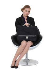 Serious businesswoman sitting with a briefcase