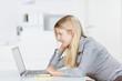 lächelnde frau im büro schaut auf laptop